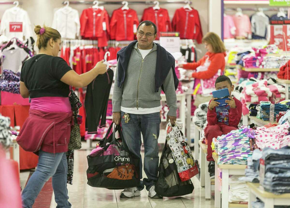 Shoppers Manuel Orellano, center, with his daughter Marcela, left, and her son Manuel, 6, shop for children's clothing at JCPenney at the Glendale Galleria shopping mall in Glendale, Calif.