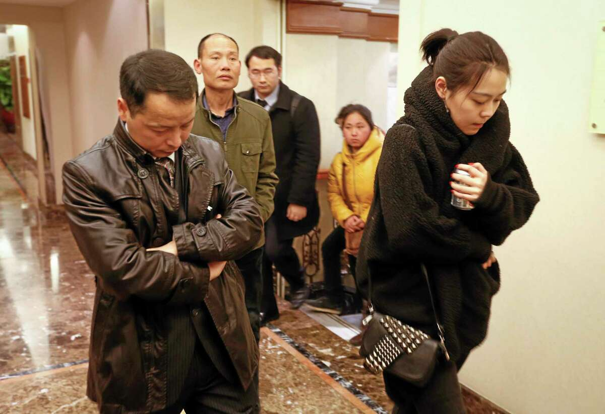 Family members arrive at a hotel which is prepared for relatives or friends of passengers aboard a missing airplane, in Beijing, China, Sunday, March 9, 2014. Search teams across Southeast Asia scrambled on Saturday to find a Malaysia Airlines Boeing 777 with 239 people on board that disappeared from air traffic control screens over waters between Malaysia and Vietnam early that morning. (AP Photo/Vincent Thian)