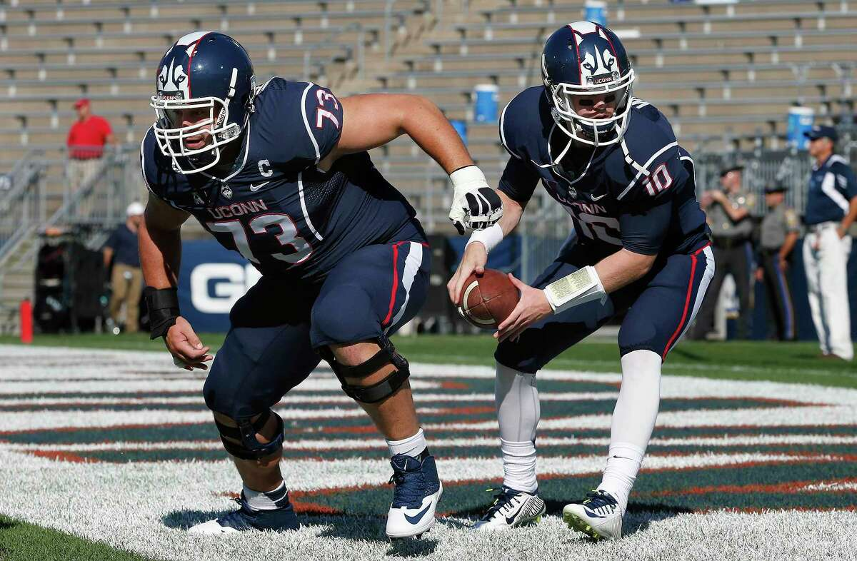 UConn senior offensive lineman Alex Mateas runs drills with quarterback Chandler Whitmer before a Sept. 27 game against Temple in East Hartford.