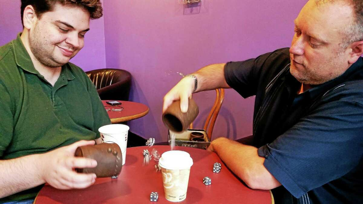 Matthew Brunell and Ryan Patrick Casey, executive director of the Chippens Group, play a dice-based strategy game in a public coffee house in the Middletown community. Casey teaches Brunell socialization skills and strategies that benefit a young man with autism.