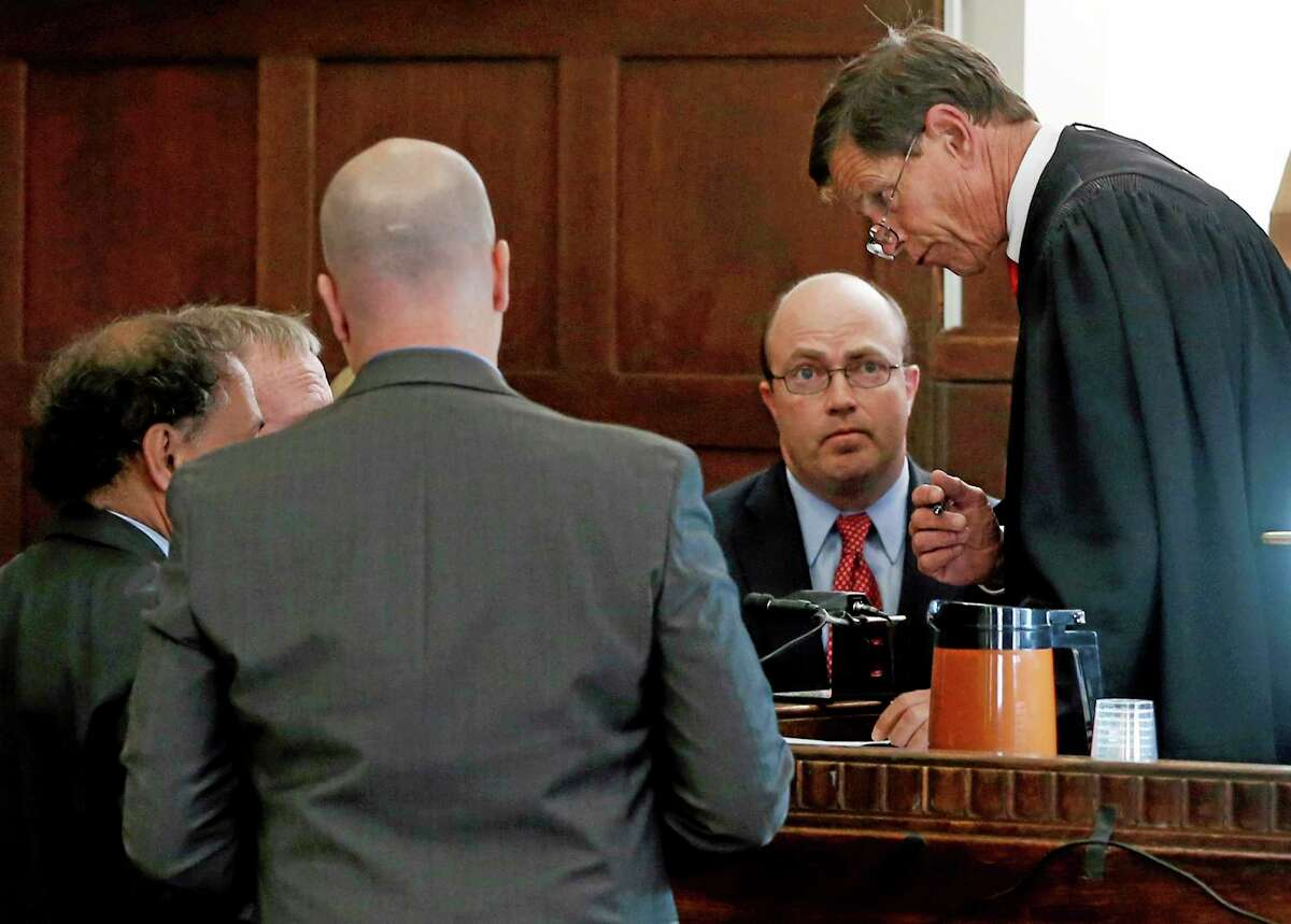 Judge Jeffrey Locke, far right, speaks to attorneys during a sidebar at a pretrial hearing for former New England Patriots player Aaron Hernandez Thursday in Suffolk Superior Court in Boston.