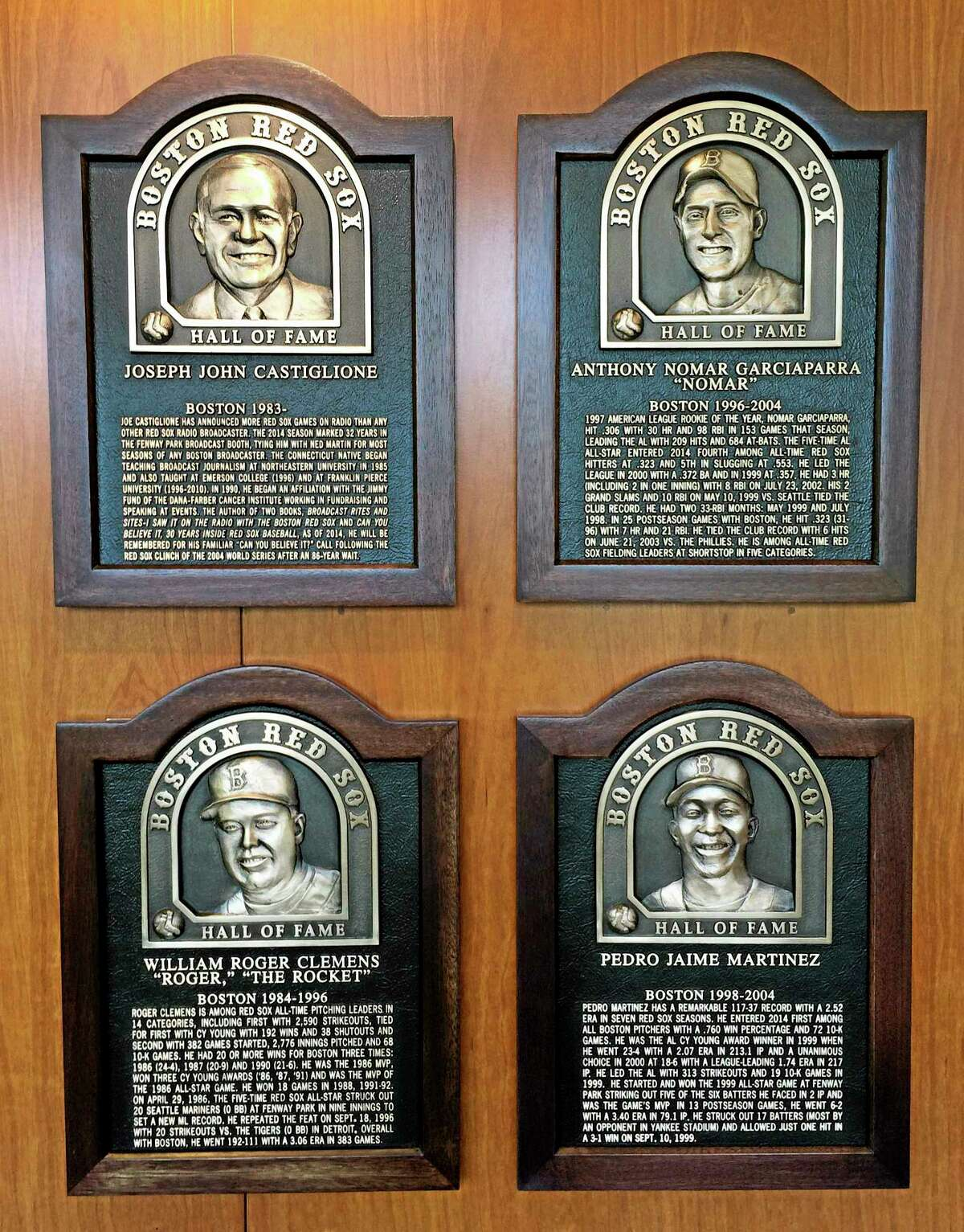 Plaques for 2014 Boston Red Sox Hall of Fame inductees hang at Fenway Park Thursday in Boston. Clockwise from top left are plaques honoring broadcaster Joe Castiglione, shortstop Nomar Garciaparra, pitcher Pedro Martinez and pitcher Roger Clemens.