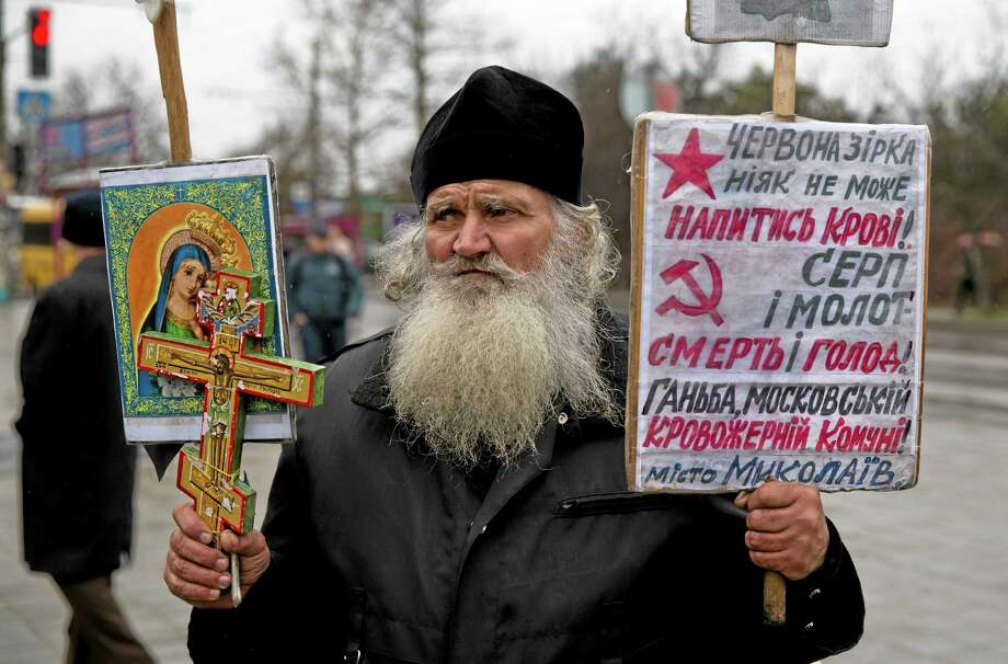 "A Ukrainian orthodox monk attends a rally against the breakup of the country in Simferopol, Ukraine, Friday, March 7, 2014. Ukraine lurched toward breakup Thursday as lawmakers in Crimea unanimously declared they wanted to join Russia and would put the decision to voters in 10 days. Banners read ""The red star needs more blood"" ""Hammer and sickle re death and hunger"" .(AP Photo/Vadim Ghirda) Photo: AP / AP"