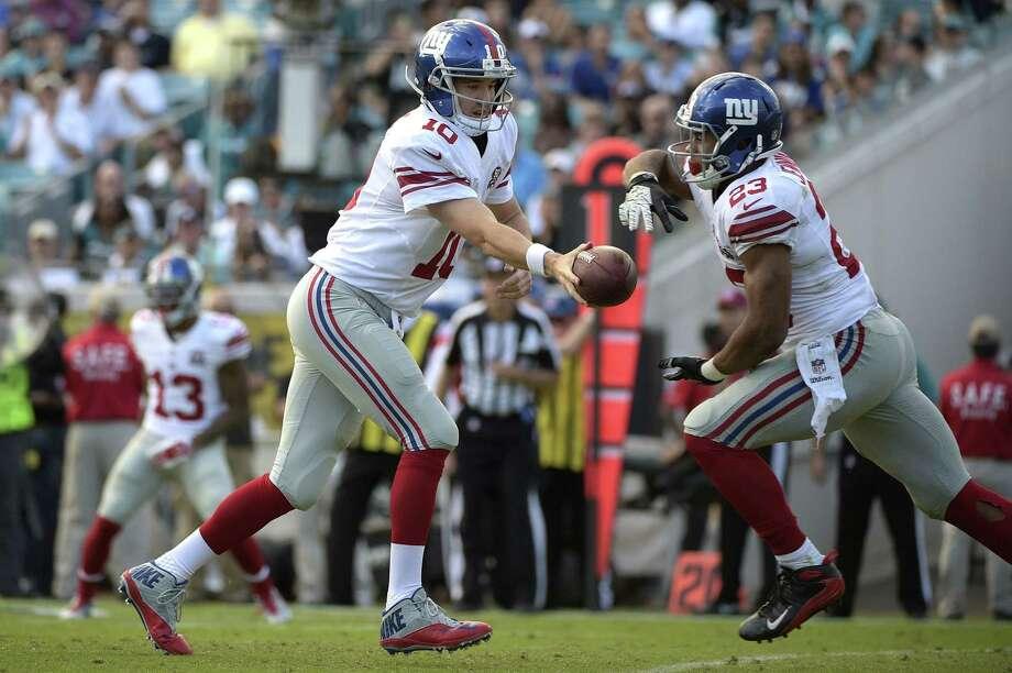 New York Giants quarterback Eli Manning hands the ball off to running back Rashad Jennings during a Nov. 30 game against the Jaguars in Jacksonville, Fla. Photo: Phelan M. Ebenhack — The Associated Press  / FR121174 AP