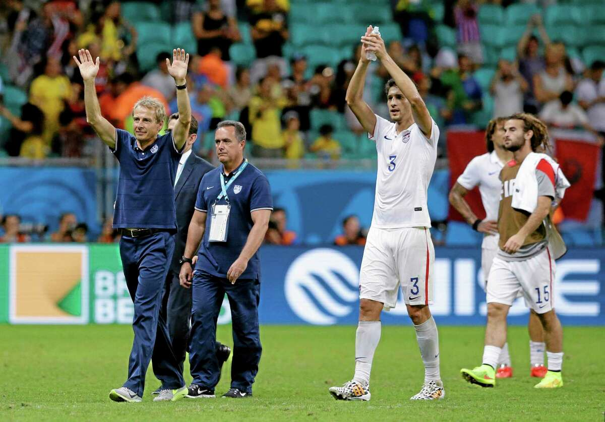 United States head coach Jurgen Klinsmann greets spectators after the World Cup round of 16 match against Belgium on July 1 in Salvador, Brazil.