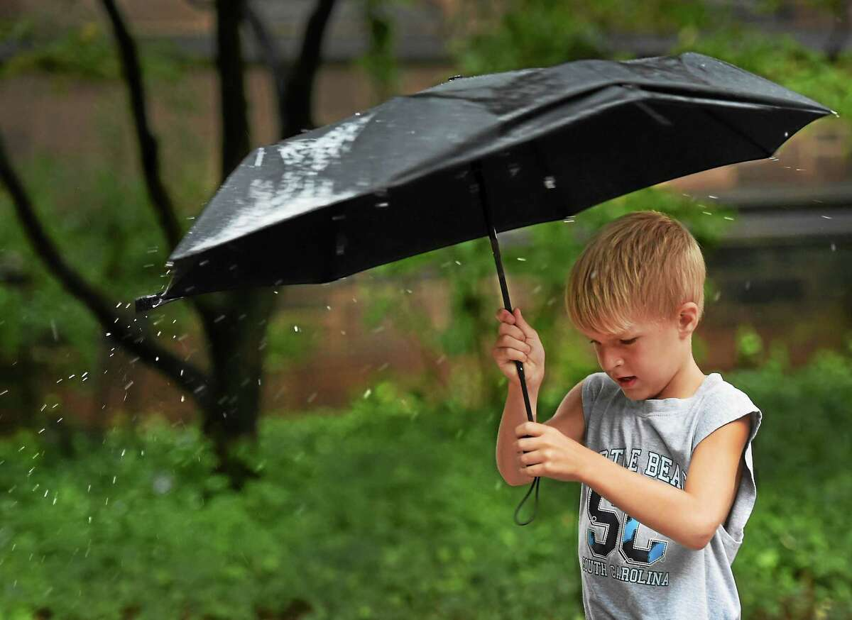 Logan Sommers, 8, of Meriden twirls his umbrella in the rain as he walks up Chapel Street in New Haven Tuesday.