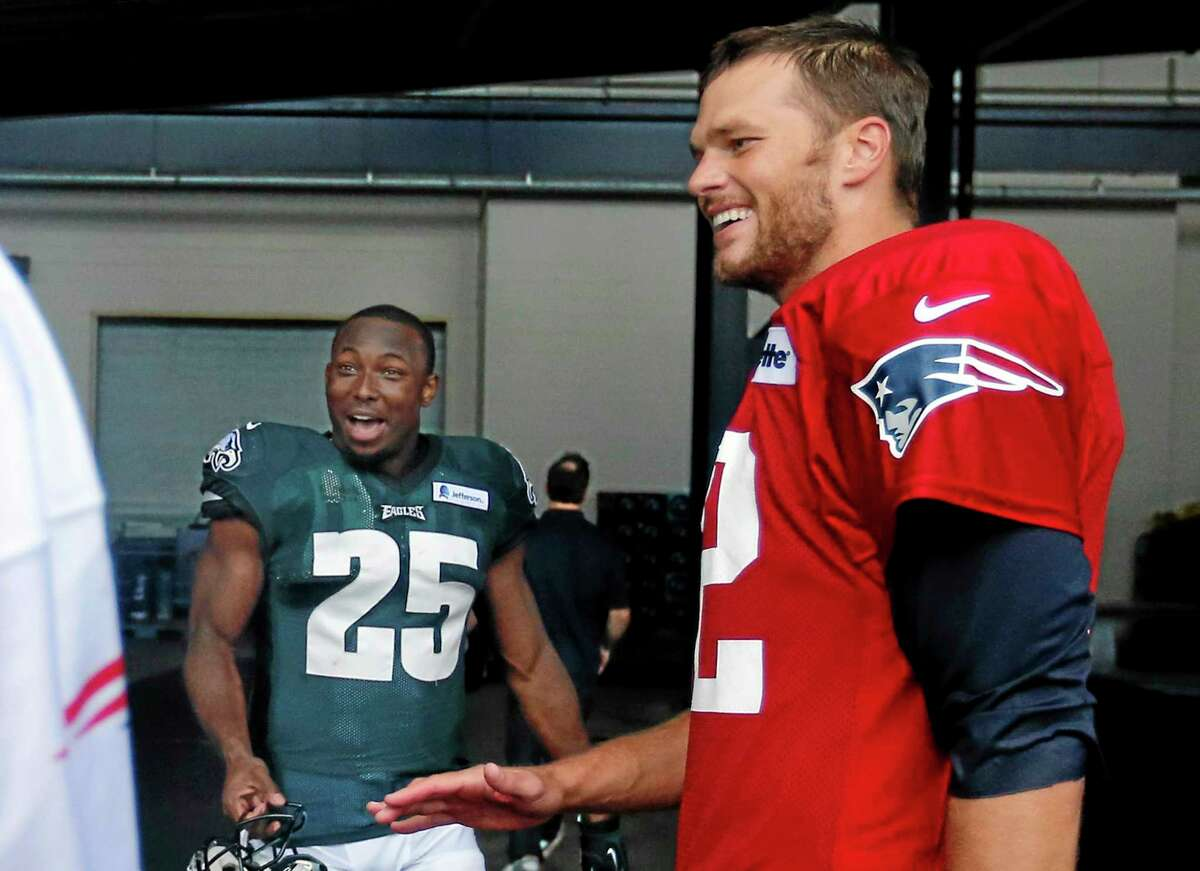 New England Patriots quarterback Tom Brady, right, and Philadelphia Eagles running back LeSean McCoy (25) chat after a joint training camp practice Wednesday in Foxborough, Mass.