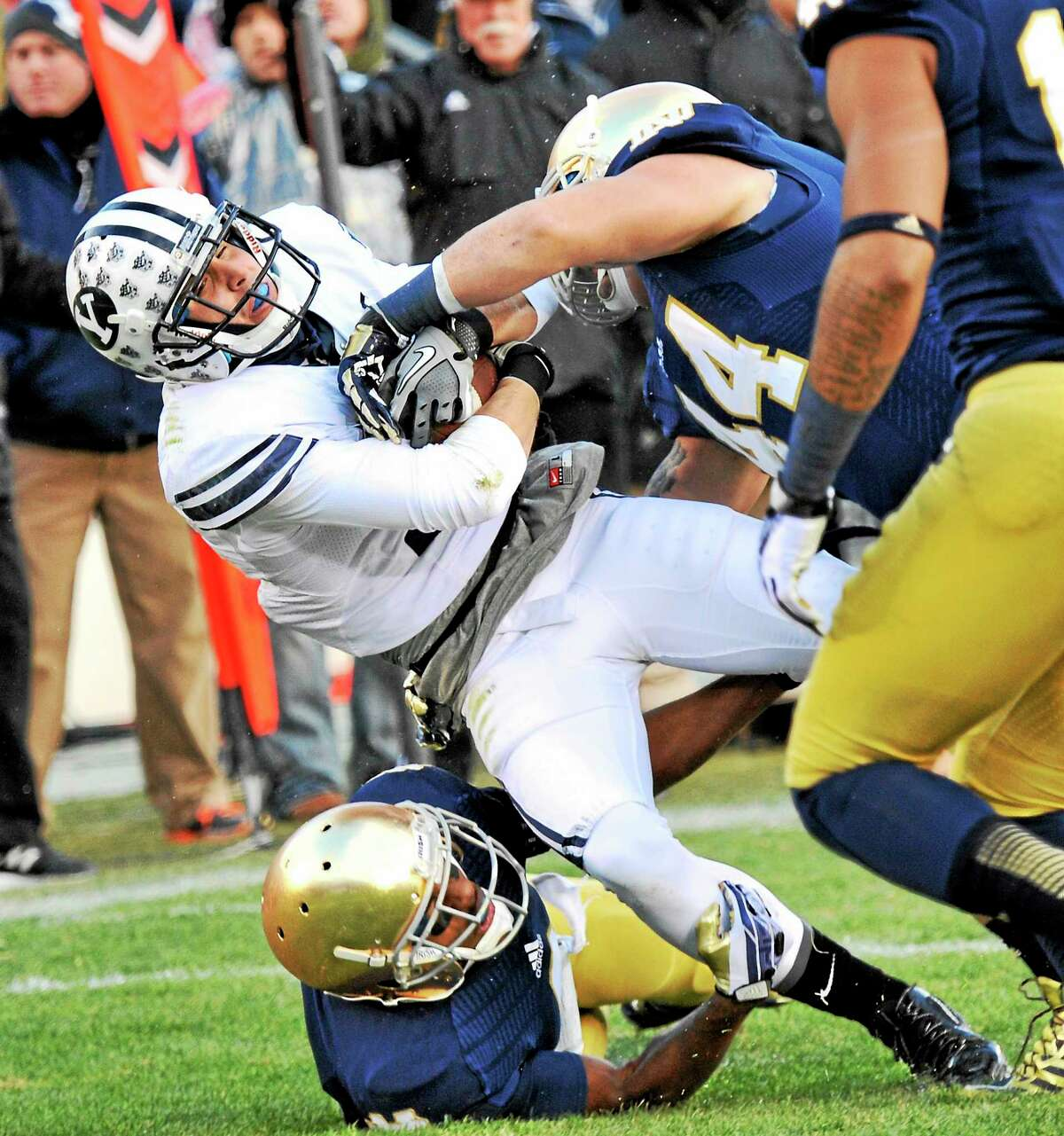 BYU wide receiver Skyley Ridley is tackled by Notre Dame linebacker Carlo Calabrese, right, and cornerback KaiVarae Russell during a Nov. 23, 2013, game in South Bend, Ind. Calabrese says new UConn football coach Bob Diaco will bring a winning culture to the Huskies.