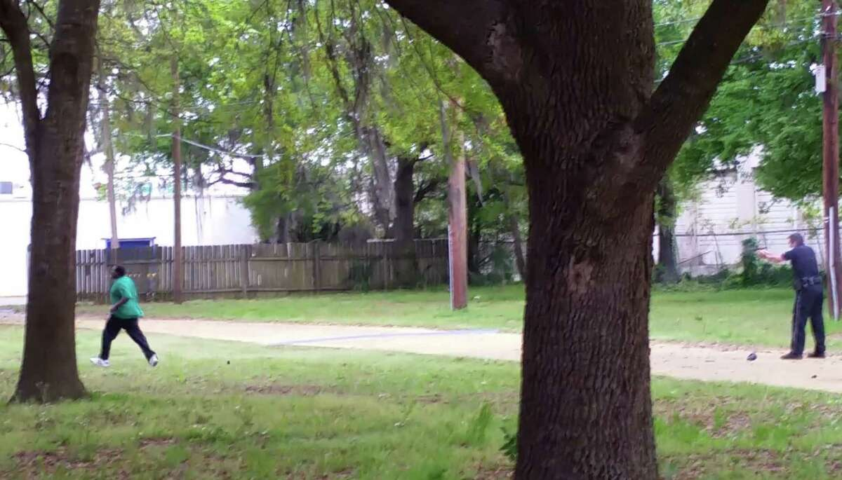 In this April 4, 2015, frame from video provided by Attorney L. Chris Stewart representing the family of Walter Lamer Scott, Scott appears to be running away from City Patrolman Michael Thomas Slager, right, in North Charleston, S.C. Slager was charged with murder Tuesday, hours after law enforcement officials viewed the dramatic video that appears to show Slager shooting a fleeing Scott several times in the back.
