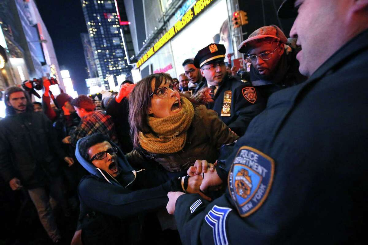 Police make arrests after protesters rallying against a grand jury's decision not to indict the police officer involved in the death of Eric Garner attempted to block traffic at the intersection of 42nd Street and Seventh Avenue near Times Square, Thursday, Dec. 4, 2014, in New York. (AP Photo/Jason DeCrow)