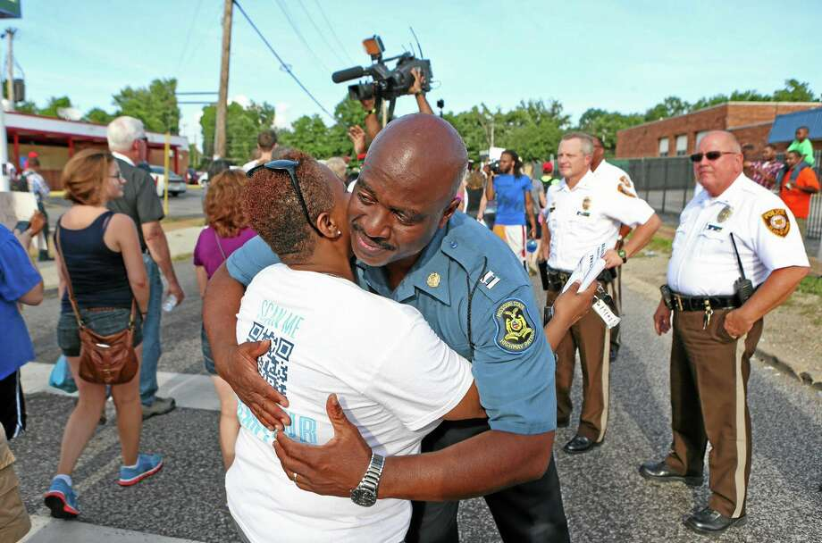 Capt. Ronald Johnson of the Missouri Highway Patrol hugs Angela Whitman, of Berkeley, Mo., on West Florissant Avenue in Ferguson, Mo., on Thursday, Aug. 14, 2014. Whitman was marching with St. Louis Metropolitan Clergy Coalition. The Missouri Highway Patrol seized control of the St. Louis suburb Thursday, stripping local police of their law-enforcement authority after four days of clashes between officers in riot gear and furious crowds protesting the death of an unarmed black teen shot by an officer. (AP Photo/St. Louis Post-Dispatch, David Carson) Photo: AP / St. Louis Post-Dispatch
