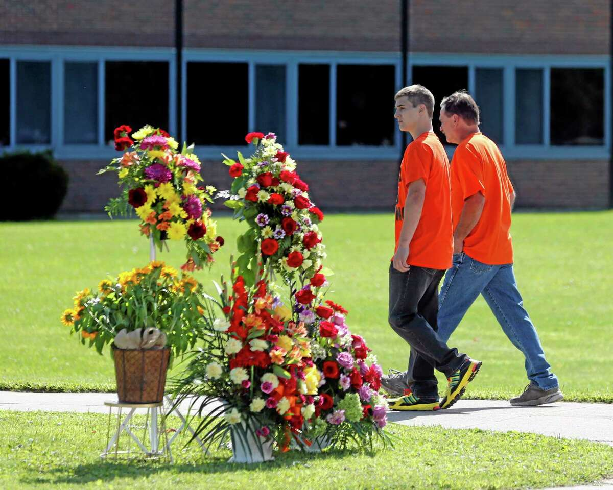 People walk to South Lewis Central School before a funeral for race car driver Kevin Ward Jr., on Thursday, Aug. 14, 2014, in Turin, N.Y. Ward died after being struck by NASCAR driver Tony Stewart's car during a race last weekend at a dirt track in western New York. (AP Photo/Mike Groll)