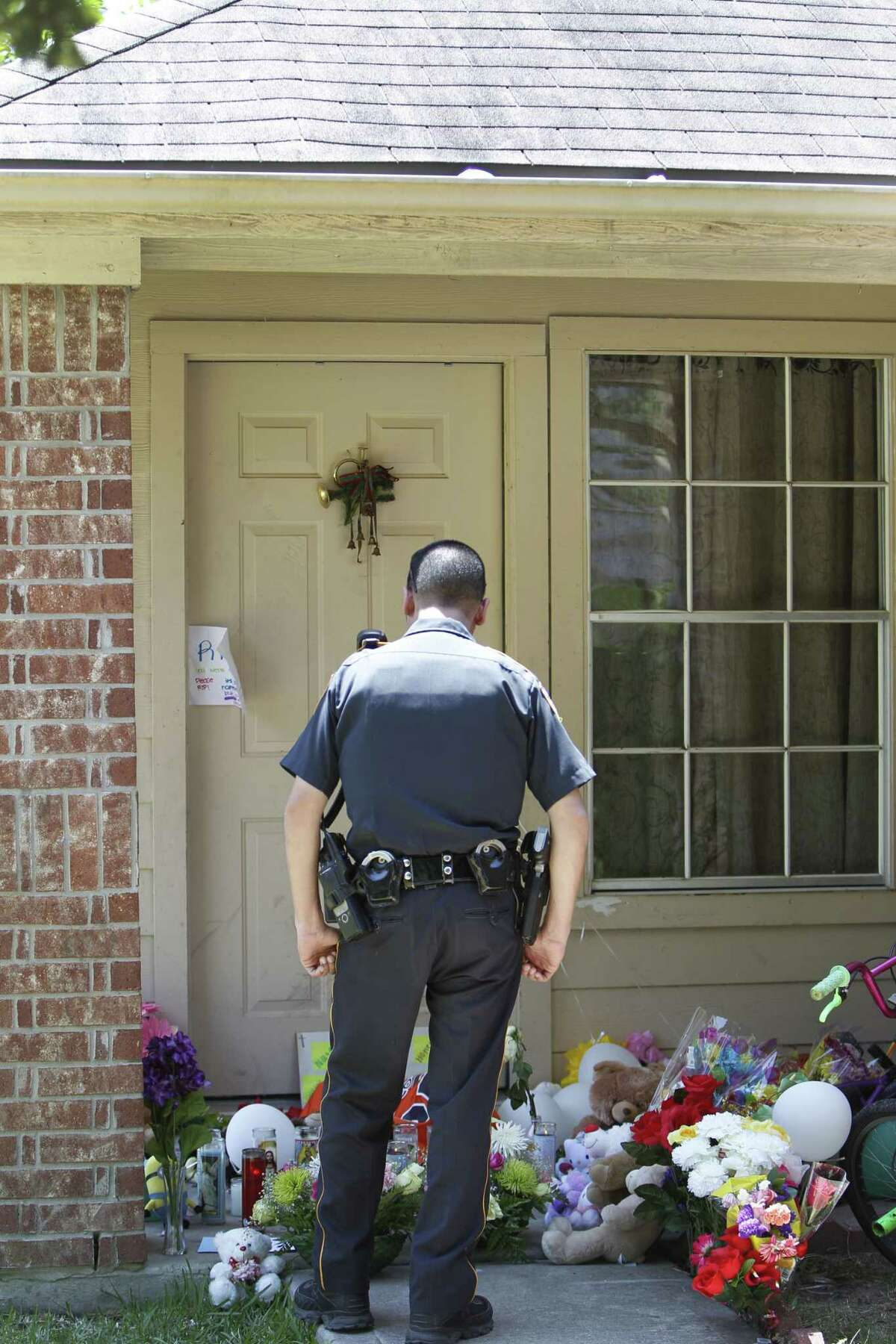 Harris County Sheriffs Officer E.A. Lopez pays his respects Monday, Aug. 10, 2015, at the scene of the home where six children and two adults were murdered Saturday night.