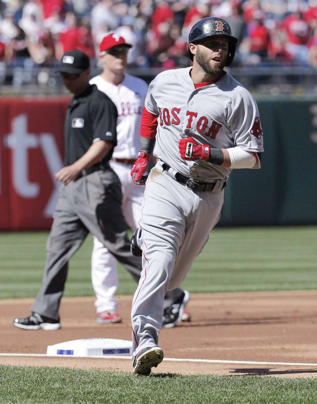 Boston Red Sox Dustin Pedroia rounds third base after hitting a solo home run during the first inning.