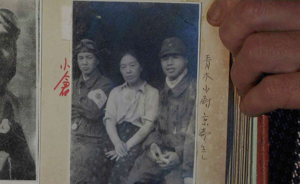 In this July 19, 2015, image taken from Associated Press Television video, Akihisa Torihama shows a 1945 photograph of his grandmother Tome Torihama, center, with Tokko pilots in Chiran in Kagoshima Prefecture, south west of Japan. Chiran served as a takeoff spot for Army pilots on a suicide attack mission in the closing days of World War II. Torihama, who died in 1992, was a mother figure for many of the pilots. Chiran is stepping up its effort to have that history remembered, and a museum there is working with the USS Missouri memorial in Hawaii to showcase the photos and letters of the dead pilots.