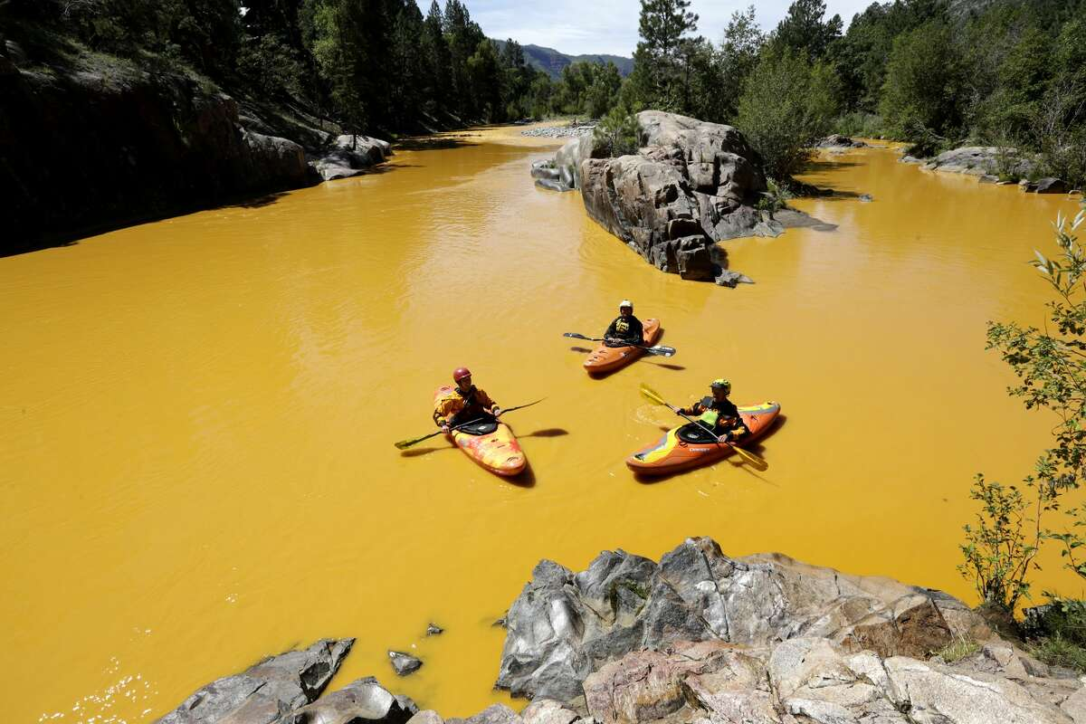 FILE - In this Thursday, Aug. 6, 2015 file photo, people kayak in the Animas River near Durango, Colo., in water colored yellow from a mine waste spill. A crew supervised by the U.S. Environmental Protection Agency has been blamed for causing the spill while attempting to clean up the area near the abandoned Gold King Mine. Tribal officials with the Navajo Nation declared an emergency on Monday, Aug. 10, as the massive plume of contaminated wastewater flowed down the San Juan River toward Lake Powell in Utah, which supplies much of the water to the Southwest.