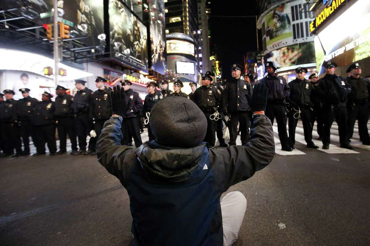 A line of police officers face a protester sitting in the road during a rally on 42nd Street near New York's Times Square against a grand jury's decision not to indict the police officer involved in the death of Eric Garner.