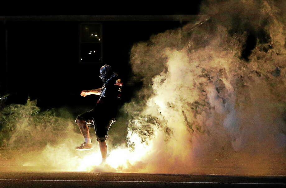 A protester kicks a smoke grenade, that had been deployed by police, back in the direction of police on Aug. 13, 2014, in Ferguson, Mo. Photo: AP Photo/Jeff Roberson  / AP2014