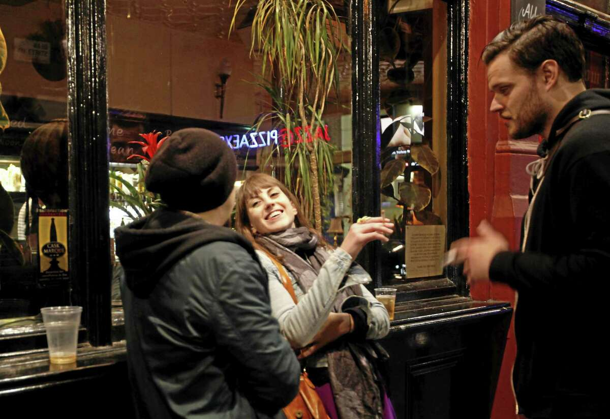Young people enjoy a smoke as they drink outside a bar in the central London area of Soho in this 2012 file photo.