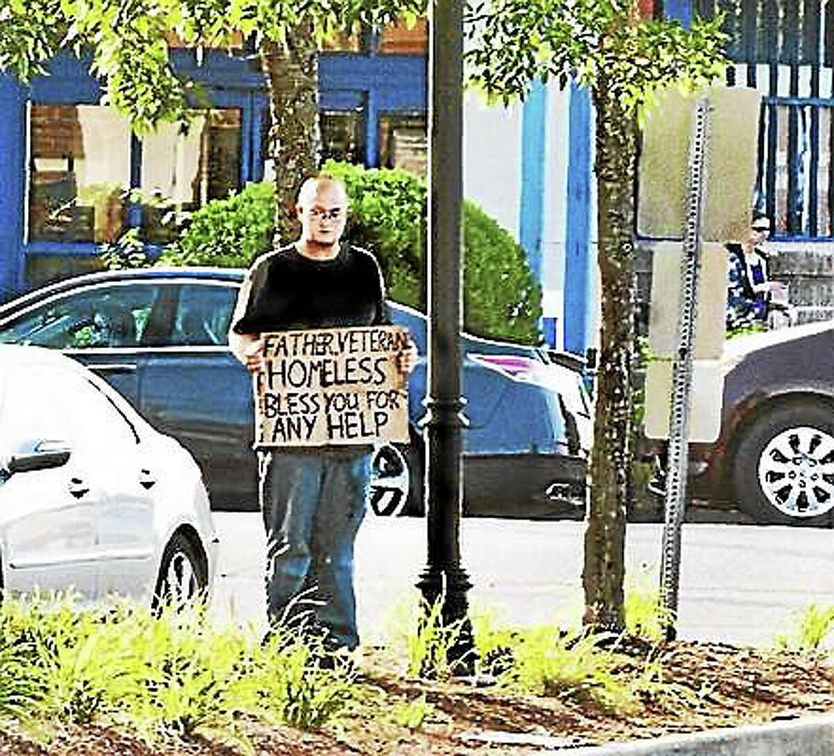 A man stands with a sign off Boston Post Road in Milford recently.