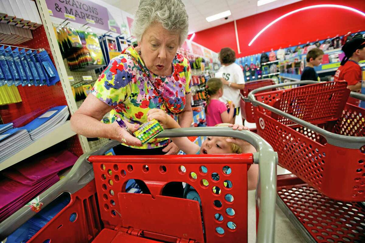 In this July 23 photo, Julie Wilkins helps her grandson, Griffin Brady, 3, put a box of crayons in a shopping cart while shopping for school supplies with her family at a Target store in Memphis, Tennessee.