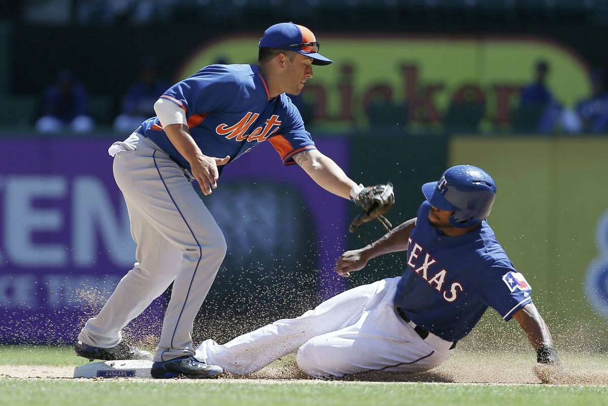New York Mets infielder Danny Muno (74) attempts to apply the tag as Texas Rangers' Delino DeShields Jr. steals second in the fifth inning of an exhibition baseball game, Saturday April 4, 2015, in Arlington, Texas. (AP Photo/Tony Gutierrez)
