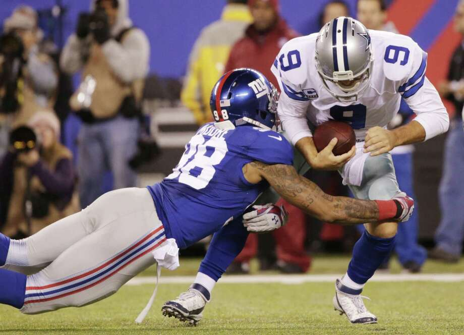 New York Giants defensive end Damontre Moore sacks Dallas Cowboys quarterback Tony Romo during a Nov. 23 game in East Rutherford, N.J. Photo: Julio Cortez — The Associated Press  / AP