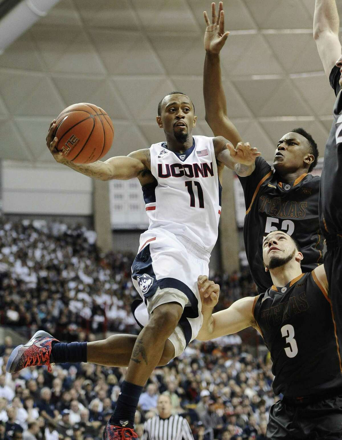 UConn's Ryan Boatright, left, passes around Texas' Myles Turner, top right, and Javan Felix during the second half of the Huskies' loss on Sunday in Storrs.