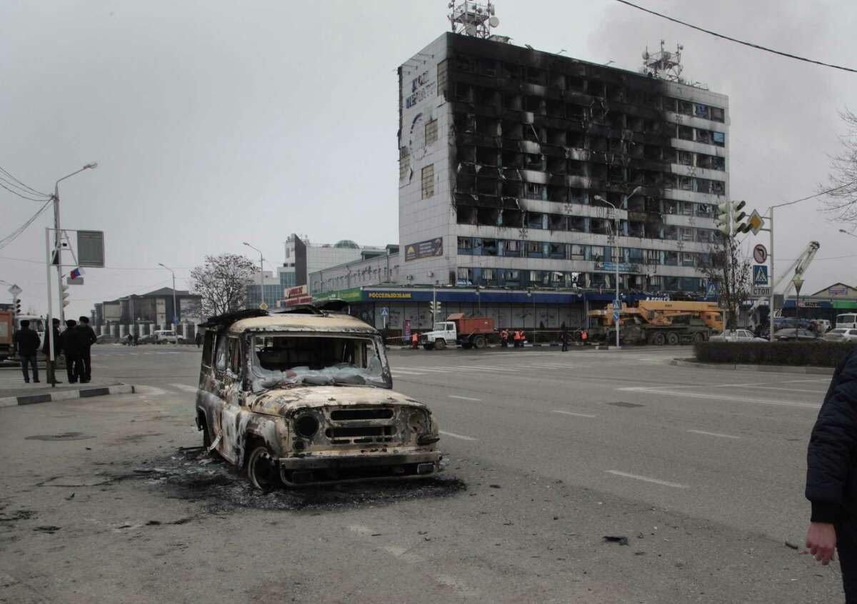 People pass a burned police car outside a burned-out publishing house in central Grozny, Russia, Thursday, Dec. 4, 2014. A gun battle broke out early Thursday in the capital of Russiaís North Caucasus republic of Chechnya, puncturing the patina of stability ensured by years of heavy-handed rule by a Kremlin-appointed leader. The violence erupted hours before Russian President Vladimir Putin began his annual state of the nation address in Moscow.(AP Photo/Musa Sadulayev)