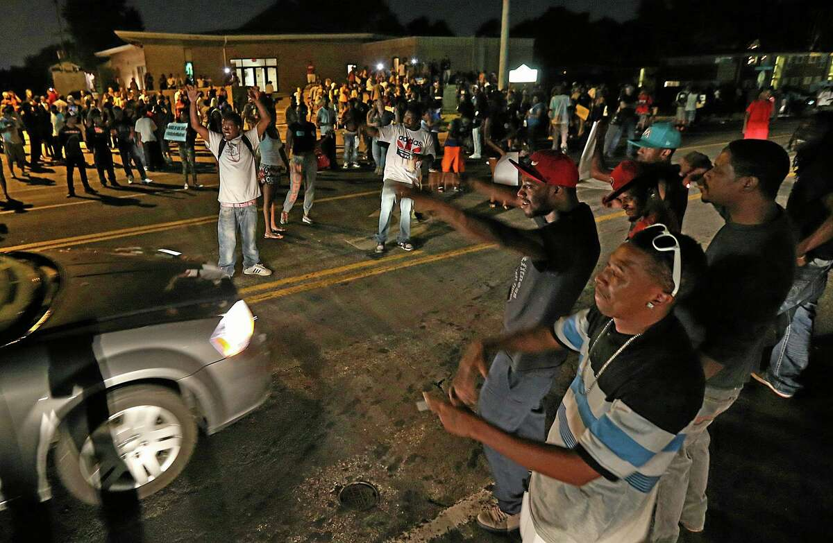 A group demonstrates along and in the middle of Chambers Rd. outside the Greater St. Mark Missionary Baptist Church after the conclusion of a gathering with Michael Brown's family and Rev. Al Sharpton on Tuesday, Aug. 12, 2014, in Dellwood.