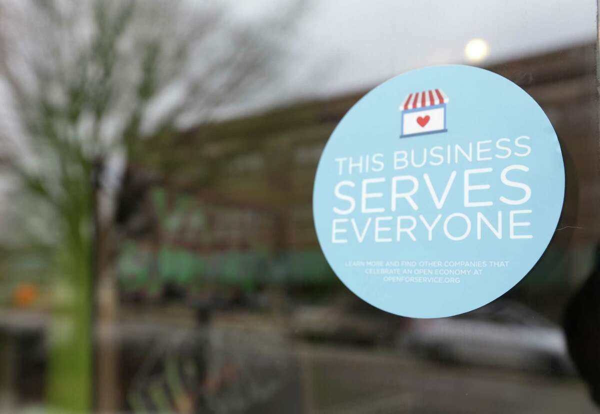 In this March 25, 2015 photo, a window sticker promising service to all is displayed in opposition to the state new religious objections law in downtown Indianapolis.