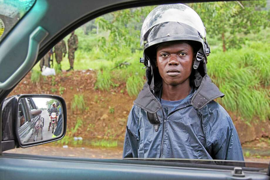In this photo taken on Tuesday, Aug 12, 2014, a Sierra Leonean Policeman stands at a road block as movement on all roads leaving towns or cities are controlled by government workers, on the outskirts of Kenema in the Eastern Province around 300km, (186 miles),  from the capital city of Freetown in Sierra Leone.  Over the decades, Ebola cases have been confirmed in 10 African countries, including Congo where the disease was first reported in 1976. But until this year, Ebola had never come to West Africa.  (AP Photo/ Michael Duff) Photo: AP / AP