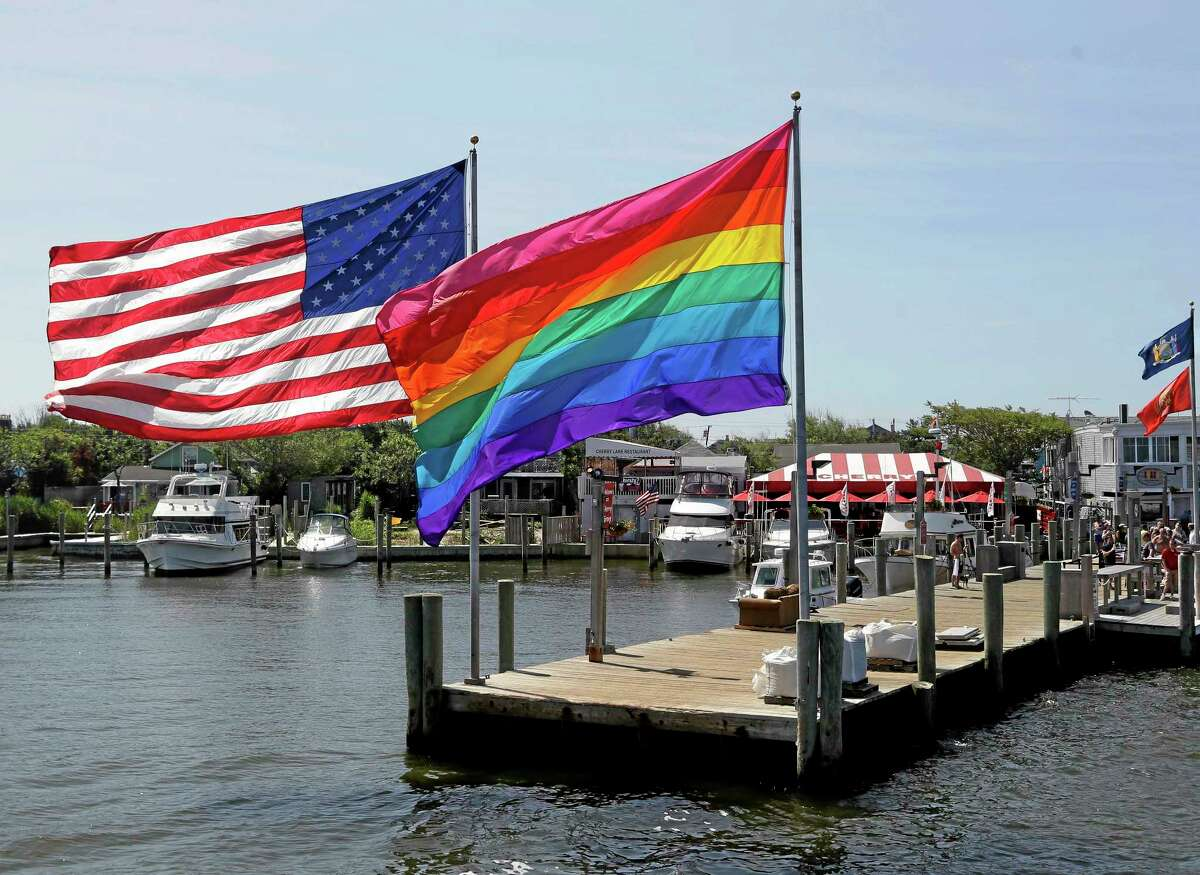 In this June 23, 2013, photo, an American flag and a LGBT Rainbow flag are displayed on the ferry dock in the Fire Island community of Cherry Grove, N.Y.