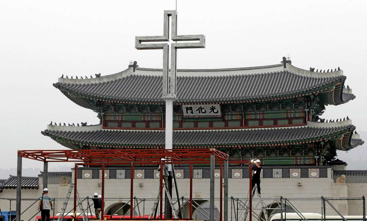 Workers set up a platform in prepare for a special holy mass by Pope Francis in front of the Gwanghwamun, the main gate of the 14th-century Gyeongbok Palace, in Seoul, South Korea, Wednesday, Aug. 13, 2014. Pope Francis is scheduled to make a five-day trip to South Korea, starting Aug. 14 to participate in a Catholic youth festival and to preside over a beatification ceremony for 124 Korean martyrs. (AP Photo/Lee Jin-man)
