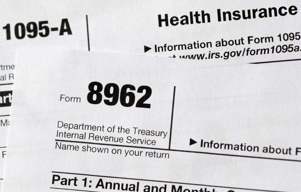 This Aug. 21, 2014 file photo shows health care tax forms 8962 and 1095-A.