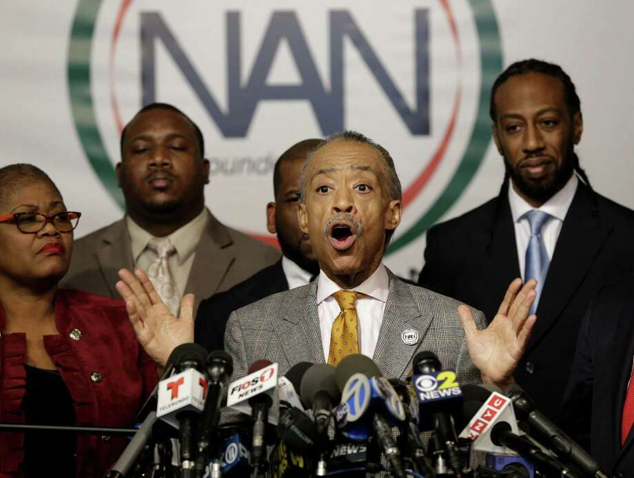 """Rev. Al Sharpton speaks during a news conference at the National Action Network headquarters in New York, Thursday, Dec. 4, 2014. National Urban League President Marc Morial calls the lack of an indictment in the Eric Garner case """"a travesty of justice."""" Sharpton said that a civil rights summit will be held following a Dec. 13 march in Washington. (AP Photo/Seth Wenig) Photo: AP / AP"""