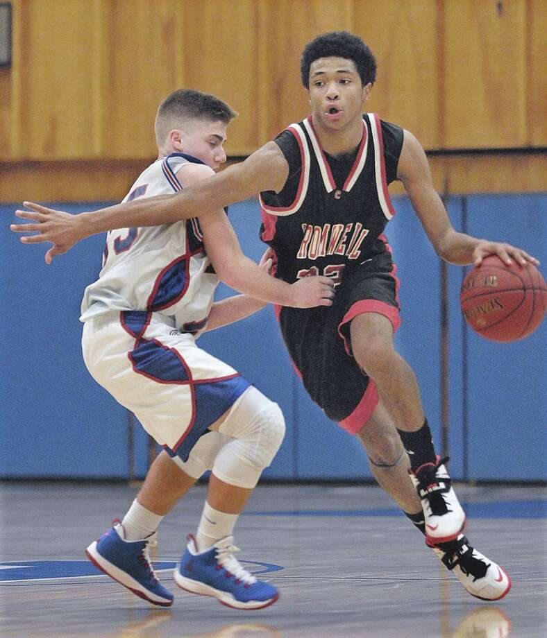 Cromwell senior guard Josh Green drives around Coginchaug sophomore guard Cameron Powers during a game earlier this season. Photo: Journal Register Co. / TheMiddletownPress