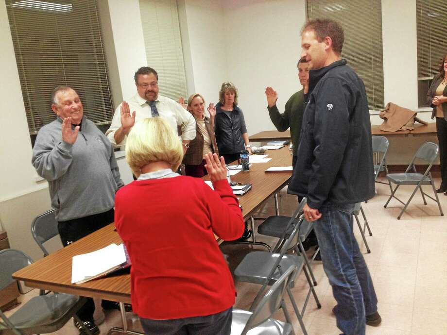 Town Clerk Darlene DiProto (back to camera) administers the oath of office to members of the Cromwell's newly established redevelopment agency. From left, the members are: Richard Nobile, Chairman Joseph Fazekas, Vice Chairwoman Ann M. Halibozek, Paul Warenda (partially obscured) and Rich Duffy. At far right is Town Attorney Kari L. Olson. Photo: Jeff Mill — The Middletown Press