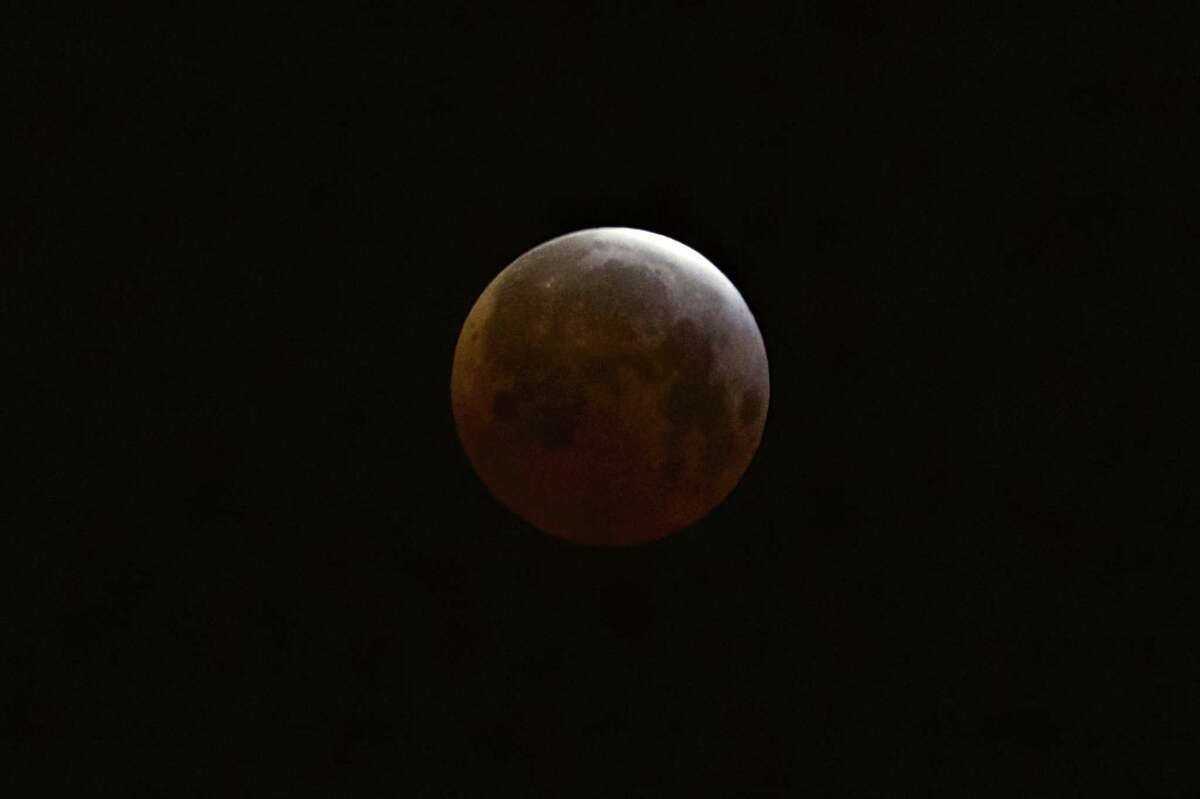 A lunar eclipse is observed as seen from Echo Park district of Los Angeles on Saturday, April 4, 2015. Early risers in the western U.S. and Canada were treated to the spectacle before dawn Saturday. The moment when the moon was completely obscured by Earth's shadow lasted several minutes, making it the shortest lunar eclipse of the century.