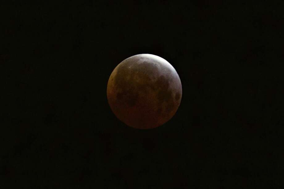 A lunar eclipse is observed as seen from Echo Park district of Los Angeles on Saturday, April 4, 2015.  Early risers in the western U.S. and Canada were treated to the spectacle before dawn Saturday. The moment when the moon was completely obscured by Earth's shadow lasted several minutes, making it the shortest lunar eclipse of the century. Photo: (AP Photo/Damian Dovarganes) / AP