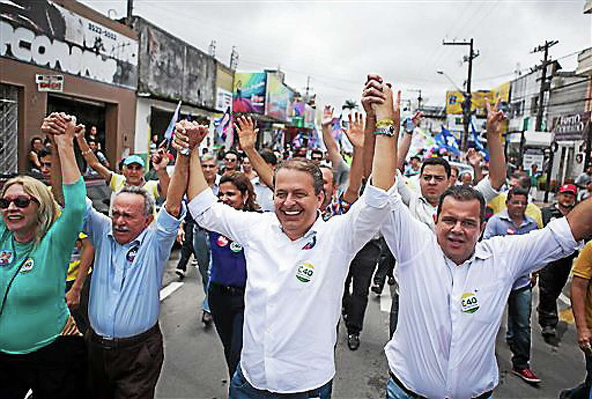 In this Aug. 8, 2014 photo released by the Partido Socialista Brasilero, PSB, Brazilian presidential candidate Eduardo Campos, center, campaigns in Arapiraca, Brazil. The PSB presidential candidate died Wednesday, Aug. 13, 2014, when the small plane that was carrying him and several campaign officials plunged into a residential neighborhood in the port city of Santos, a City Hall official there said. (AP Photo/Partido Socialista Brasilero, Alexandre Severo)