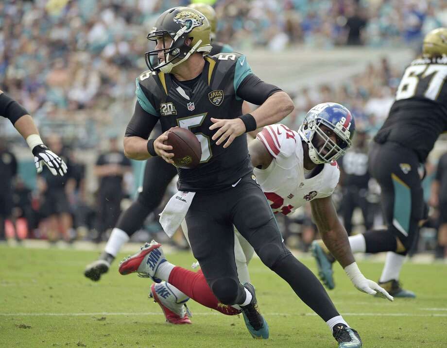 Jaguars quarterback Blake Bortles scrambles away from New York Giants defensive end Robert Ayers during Sunday's game in Jacksonville, Fla. Photo: Phelan M. Ebenhack — The Associated Press  / FR121174 AP