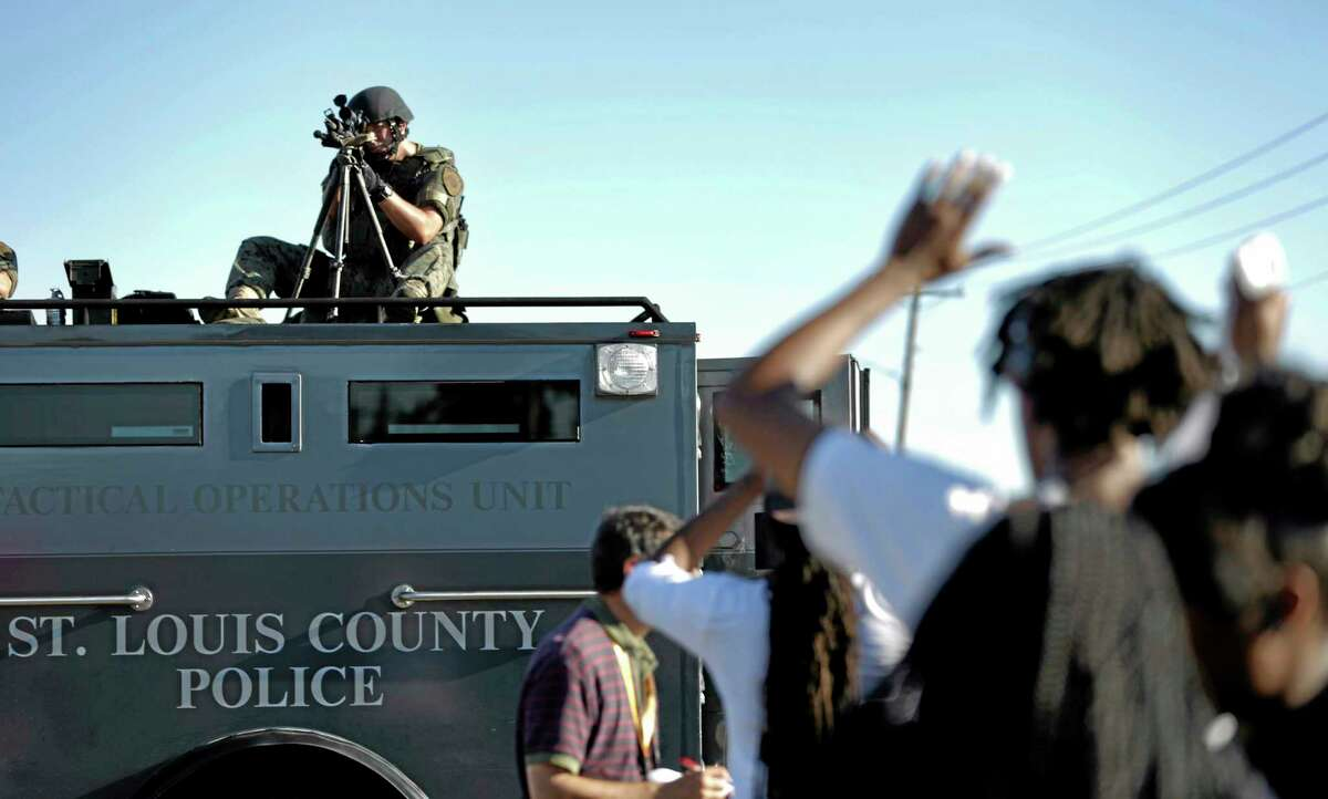 A member of the St. Louis County Police Department points his weapon in the direction of a group of protesters in Ferguson, Mo. on Wednesday, Aug. 13, 2014. On Saturday, Aug. 9, 2014, a white police officer fatally shot Michael Brown, an unarmed black teenager, in the St. Louis suburb.