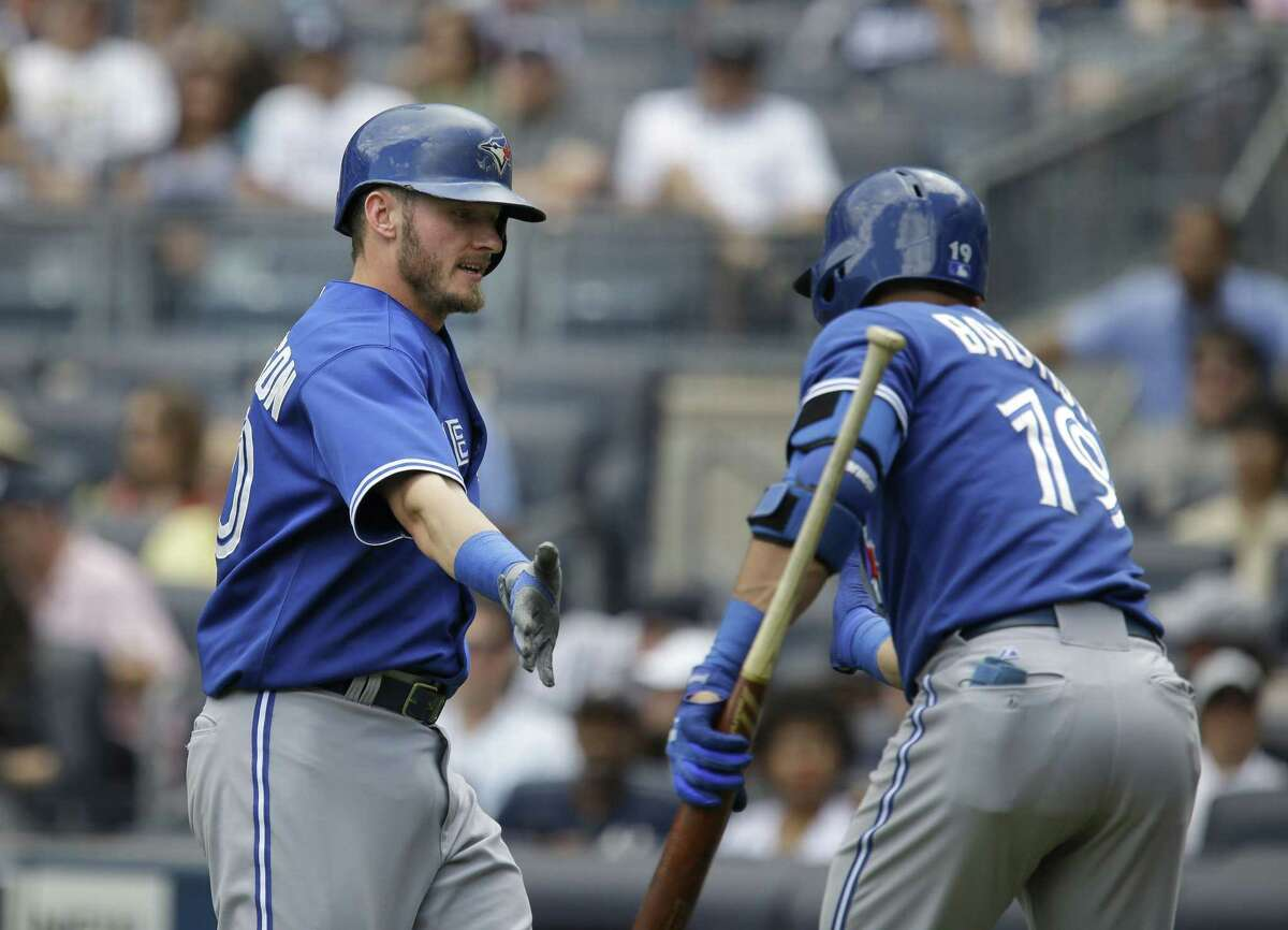 Jose Bautista, right, celebrates with Josh Donaldson during the first inning of the Toronto Blue Jays' 2-0 win over the Yankees on Sunday in New York. Both Bautista and Donaldson hit solo homers.