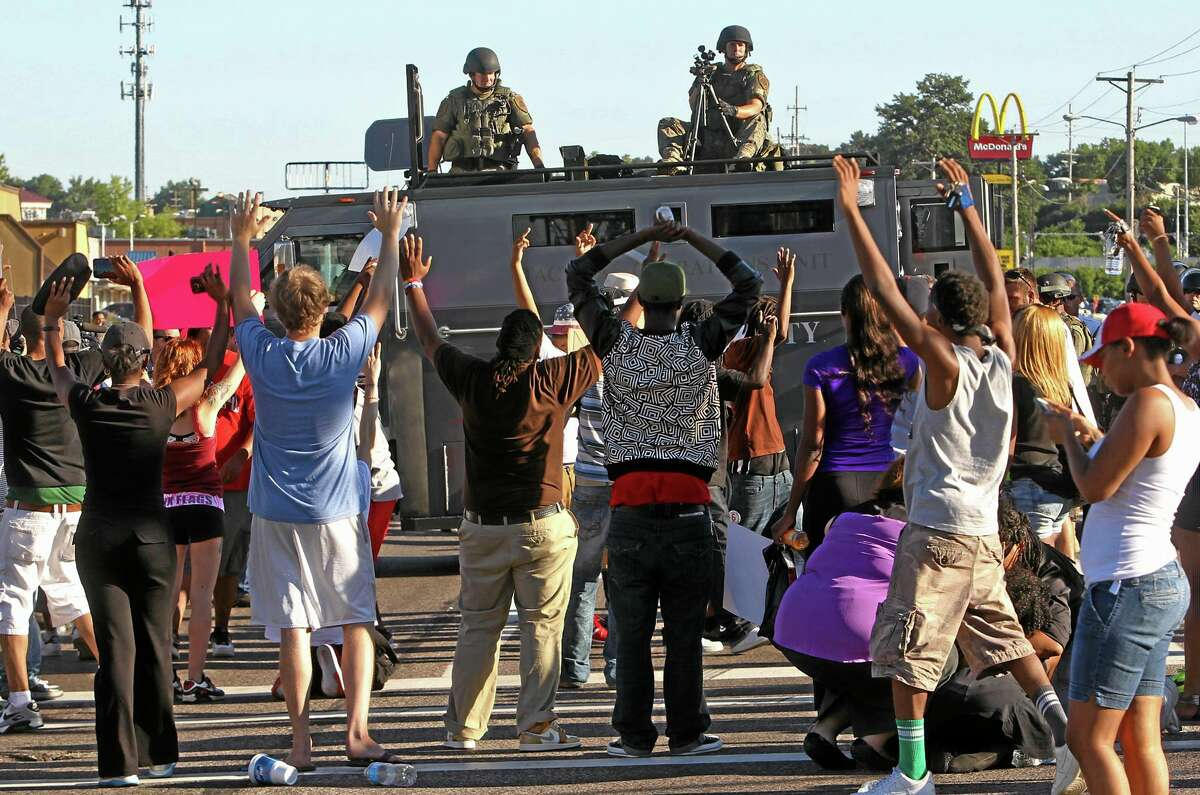 Protesters raise their hands in front of police atop an armored vehicle in Ferguson, Mo. on Wednesday, Aug. 13, 2014. On Saturday, Aug. 9, 2014, a police officer fatally shot Michael Brown, an unarmed black teenager, in the St. Louis suburb. (AP Photo/St. Louis Post-Dispatch, J.B. Forbes)