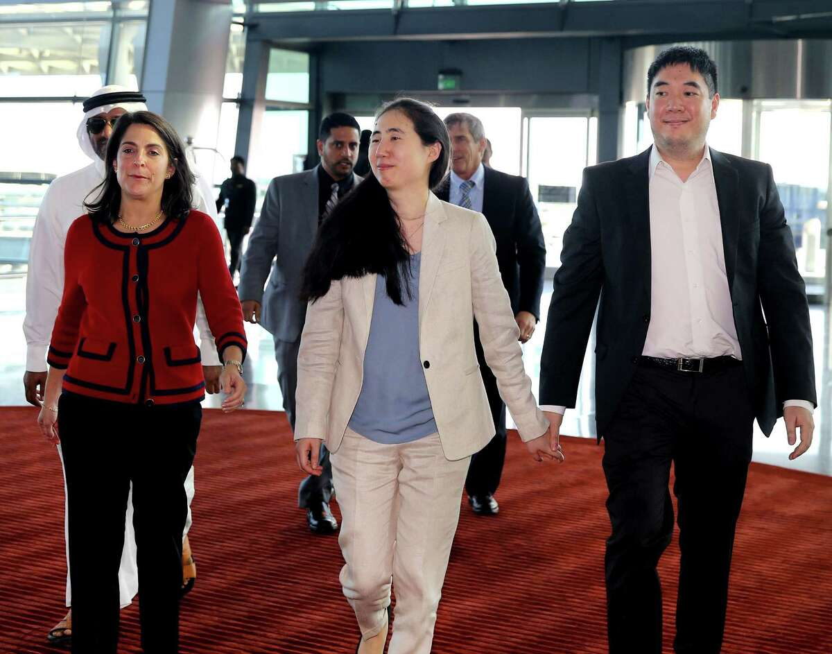 American couple Grace, center, and Matthew Huang, right, walk to their departure gate with U.S. Ambassador to Qatar, Dana Shell Smith, left, at the Hamad International Airport in Doha, Qatar, Wednesday, Dec. 3, 2014. An American couple cleared of charges in their adopted daughterís death passed through passport control Wednesday and are set to leave Qatar. (AP Photo/Osama Faisal)