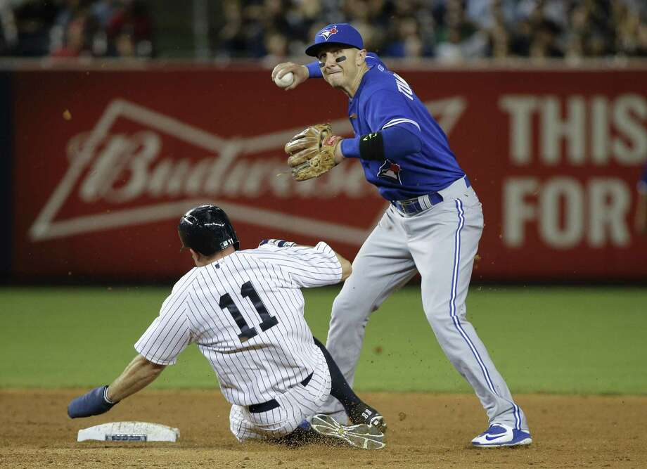Toronto Blue Jays shortstop Troy Tulowitzki turns a double play as the New York Yankees' Brett Gardner slides into second during Friday night's game. Photo: Julie Jacobson — The Associated Press  / AP