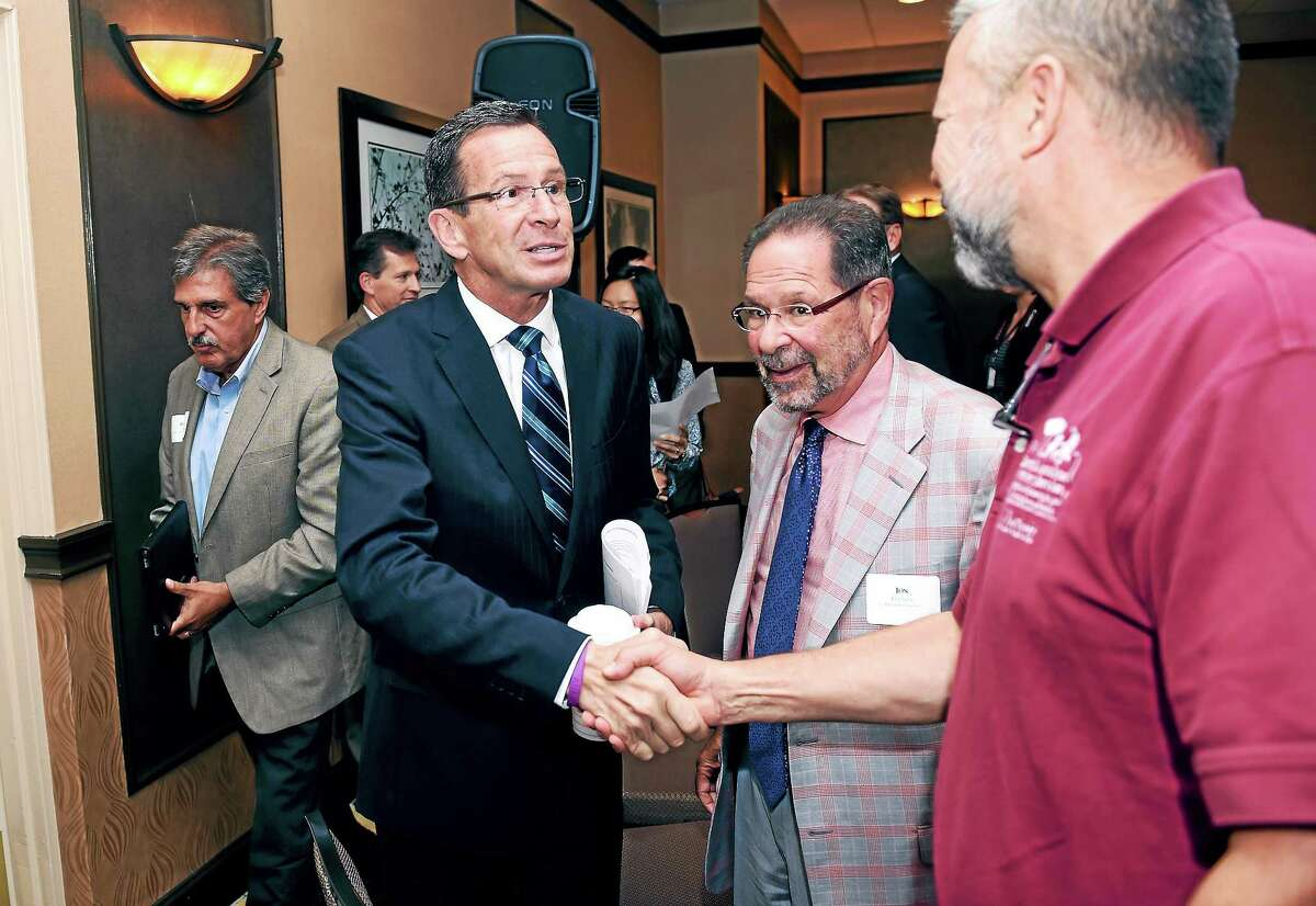 Connecticut Governor Dannel P. Malloy (center) shakes hands with Chip Beckett, Vice Chairman of the Capitol Region Council of Governments, at a Transportation Forum in North Haven, Connecticut, on Monday September 15, 2014.
