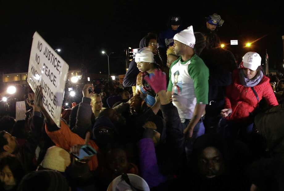 FILE - In this Nov. 24, 2014 file photo Louis Head, center right, Michael Brown's stepfather, and Brown's mother Lesley McSpadden, center left, react as  they listen to the announcement that a grand jury decided not to indict Ferguson police officer Darren Wilson who fatally shot 18-year-old  Brown. Brown has apologized for angry comments he made after the decision was announced, but said his remarks had nothing to do with the arson and looting that ravaged Ferguson and the surrounding area. (AP Photo/Charlie Riedel, File) Photo: AP / AP