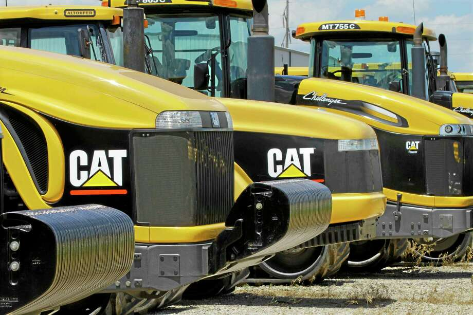 FILE - In this June 20, 2012 file photo, earth-moving tractors and equipment made by Peoria, Ill.-based Caterpillar Inc. are seen in Clinton, Ill.  Caterpillar and several mining companies have evacuated employees from Liberia. British Airlines has canceled flights to the region. Exxon and Chevron say theyíre waiting to see whether public health authorities can contain the Ebola outbreak in three West African countries. (AP Photo/Seth Perlman, File) Photo: AP / AP